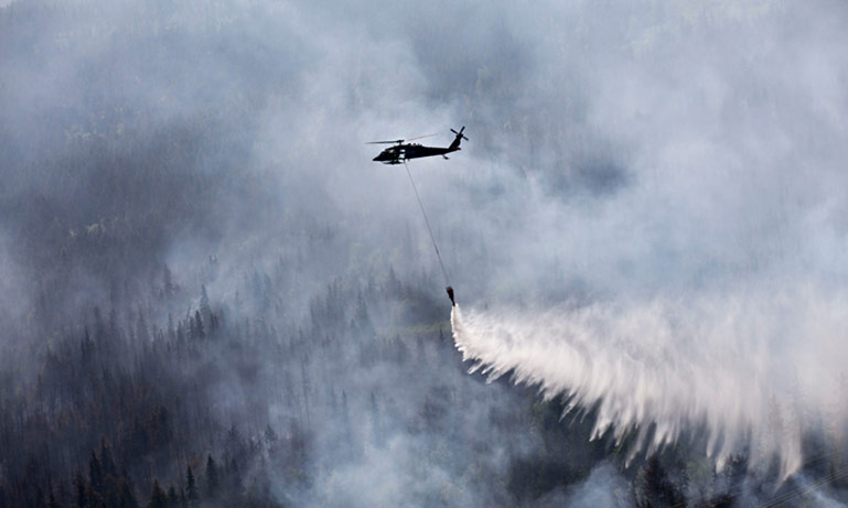 A Blackhawk helicopters pours water on the Stetson Creek Fire near Cooper Landing, Alaska on June 17, 2015